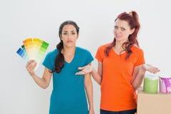 Amis confus choisissant la couleur pour peindre une salle Photo libre de droits