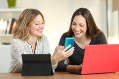 Amis consultant les dispositifs multiples à la maison images libres de droits