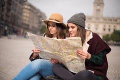 Amis consultant une carte de ville Images stock