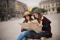 Amis consultant une carte de ville Photos libres de droits
