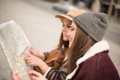 Amis consultant une carte de ville Photographie stock libre de droits