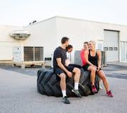 Amis convenables conversant tout en détendant sur le pneu Photographie stock libre de droits