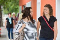 Amis conversant tout en marchant sur le trottoir Photographie stock libre de droits