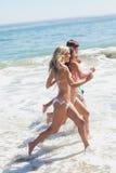 Amis courant à la plage Photos libres de droits