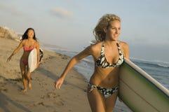 Amis courant avec des planches de surf Images libres de droits