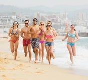 Amis courant dans les vêtements de bain à la plage de mer Photographie stock