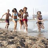 Amis courant sur la plage Image libre de droits