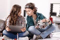 Amis curieux à l'aide des instruments et des dispositifs modernes à la maison Images libres de droits