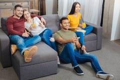 Amis curieux souriant tout en observant un programme intéressant à la TV Images stock