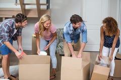 Amis déballant le carton dans la nouvelle maison Photo stock