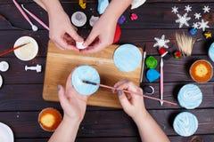Amis décorant les petits gâteaux, vue d'en haut Culinaire de famille Photographie stock