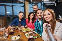 Amis décrivant par le bâton de selfie au restaurant Photographie stock libre de droits