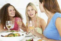 Amis détendant à la maison prenant le déjeuner Images stock