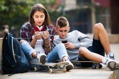 Amis détendant avec des téléphones portables Photo stock