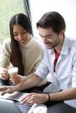 Amis détendant avec une tasse de café et travaillant sur l'ordinateur portable Images libres de droits