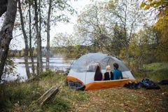 Amis détendant dans la tente sur au bord du lac Photos libres de droits