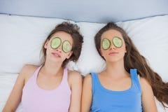 Amis détendant dans le lit avec le concombre sur des yeux Photo stock