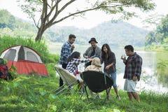 Amis détendant en dehors des tentes sur le camping Photos stock