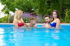 Amis détendant ensemble dans la piscine Photographie stock