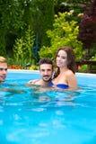 Amis détendant ensemble dans la piscine Photographie stock libre de droits