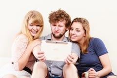 Amis détendant l'Internet de lecture rapide sur le comprimé Photos libres de droits