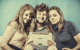 Amis détendant l'Internet de lecture rapide sur le comprimé Photo stock