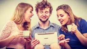 Amis détendant l'Internet de lecture rapide sur le comprimé Images stock