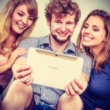 Amis détendant l'Internet de lecture rapide sur le comprimé Photo libre de droits