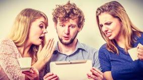 Amis détendant l'Internet de lecture rapide sur le comprimé Photographie stock libre de droits