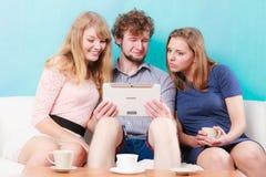 Amis détendant l'Internet de lecture rapide sur le comprimé Image stock