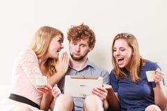 Amis détendant l'Internet de lecture rapide sur le comprimé Image libre de droits