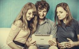 Amis détendant l'Internet de lecture rapide sur le comprimé Photographie stock
