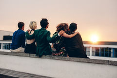 Amis détendant sur la terrasse dans la soirée Image stock