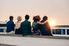 Amis détendant sur la terrasse dans la soirée Image libre de droits
