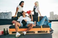 Amis détendant sur le toit Image stock
