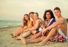 Amis détendant sur une plage Image libre de droits