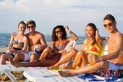 Amis détendant sur une plage Photos libres de droits