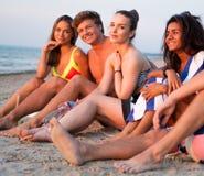 Amis détendant sur une plage Images libres de droits