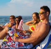 Amis détendant sur une plage Photo libre de droits