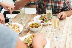 Amis dînant avec de la salade, les olives et le champagne sur la table en bois extérieure Photographie stock libre de droits
