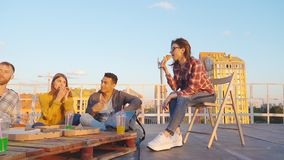 Amis dînant ou BBQ, ou partie de pizza sur le dessus de toit banque de vidéos
