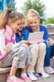 Amis d'école avec un dispositif de comprimé Photos stock