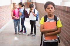 Amis d'élèves taquinant seul un élève image stock