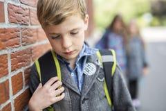 Amis d'élèves taquinant une seule école primaire d'élève Image stock