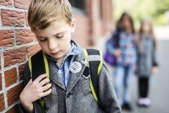 Amis d'élèves taquinant une seule école primaire d'élève Photo stock