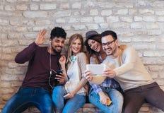 Amis d'étudiants de diversité employant le concept de dispositifs de Digital photo libre de droits