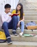 amis d'étudiants s'asseyant sur des escaliers utilisant le livre image stock