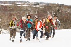 Amis d'adolescent ayant l'amusement dans la neige Photographie stock