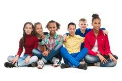 Amis d'adolescent s'asseyant sur l'embrassement de plancher Photos libres de droits