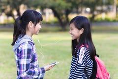 amis d'adolescentes observant le téléphone intelligent à l'école Images stock